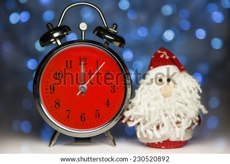 Santa Claus or Father Frost and vintage alarm clock with red dial on christmas lights background. Showing time twelve midnight - stock photo