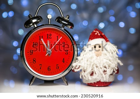 Santa Claus or Father Frost and vintage alarm clock with red dial on christmas lights background. Showing time five minutes before twelve midnight - stock photo