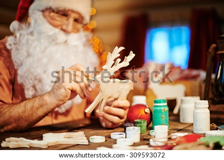 Santa Claus painting wooden deer with gouache - stock photo
