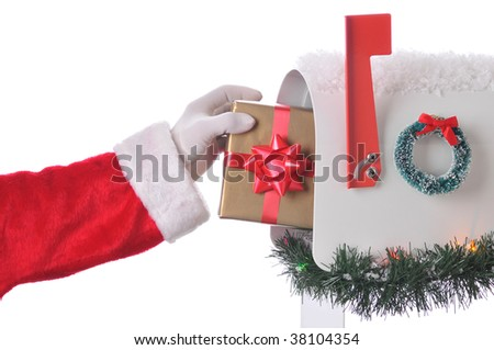 Santa Claus Placing wrapped present in mailbox that is decorated for Christmas with wreath, garland and snow - stock photo