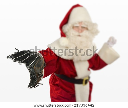 Santa Claus Playing Baseball - Santa Claus is playing with a baseball and a catcher's glove - stock photo