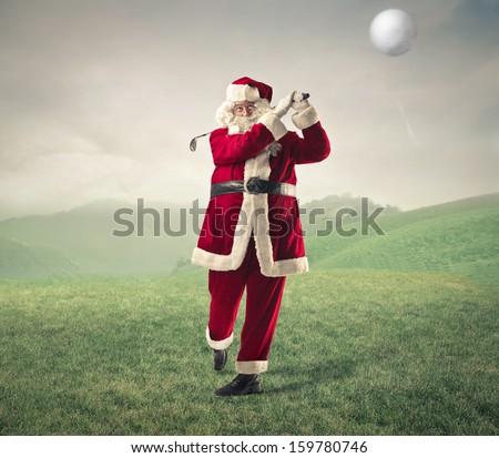 Santa Claus playing golf - stock photo
