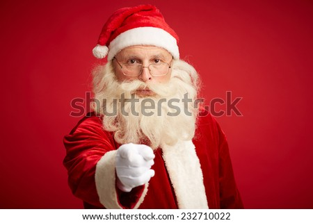Santa Claus pointing and looking at camera over red background - stock photo