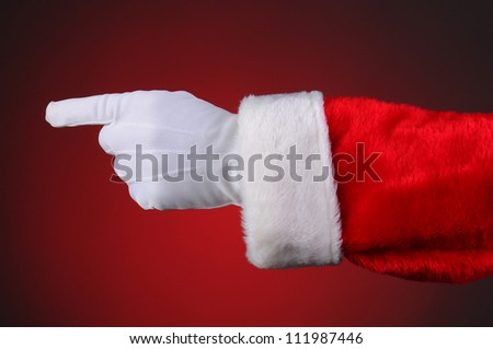 Santa Claus pointing, hand and arm only. Horizontal format over a light to dark red background.
