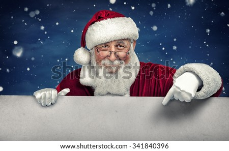 Santa Claus pointing in white blank sign with smile, on winter snow  background - stock photo