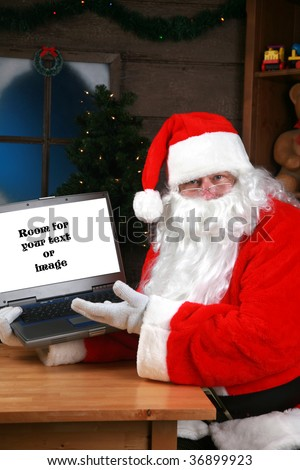 Santa Claus points to his laptop computer with room for your text or image - stock photo