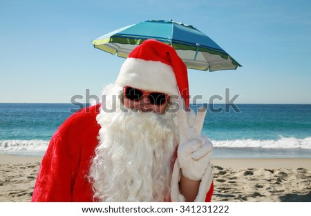Santa Claus portrait while wearing Sun Glasses and Vacationing on a Beautiful Beach with the Blue Ocean behind him. Focus on Santa's Face. - stock photo
