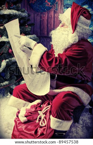 Santa Claus posing with a list of presents over Christmas background. - stock photo