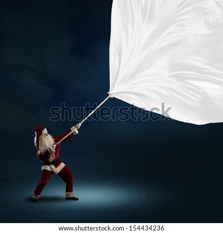 Santa Claus pulls a banner of cloth with a rope, place for text