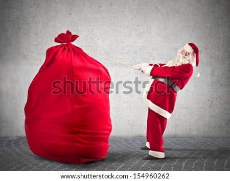 Santa Claus pulls big red sack - stock photo