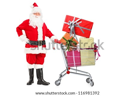 Santa Claus pushing a shopping cart full of gifts isolated on white background - stock photo