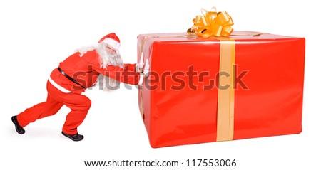 santa claus pushing big gift - stock photo
