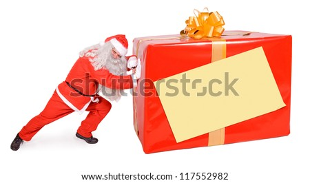 Santa Claus pushing large Christmas box isolated on white background. Big Xmas gift with empty sign on the packaging.