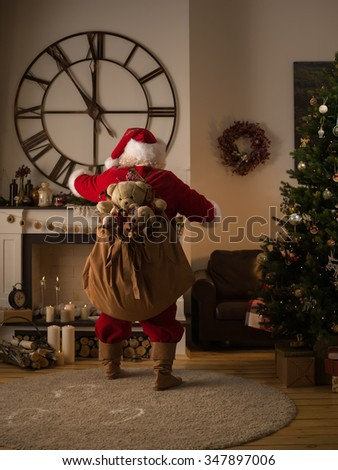 Santa Claus Putting Gifts in Socks on Fireplace at Home - stock photo