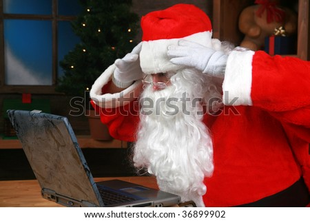 Santa Claus reacts to his e-mail on his laptop computer - stock photo