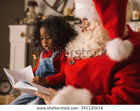 Santa Claus reading a book with cute african child near the fireplace and Christmas tree at home - stock photo