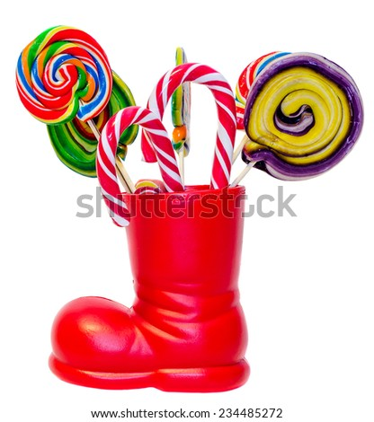 Santa Claus red boot, shoe with colored sweet lollipops, candys. Saint Nicholas boot with presents, gifts. - stock photo