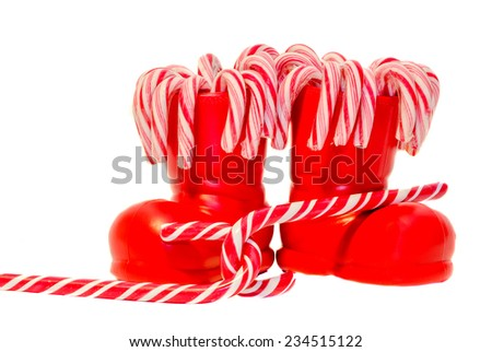 Santa Claus red boots, shoes with colored sweet lollipops, candys. Saint Nicholas boots with presents, gifts. - stock photo