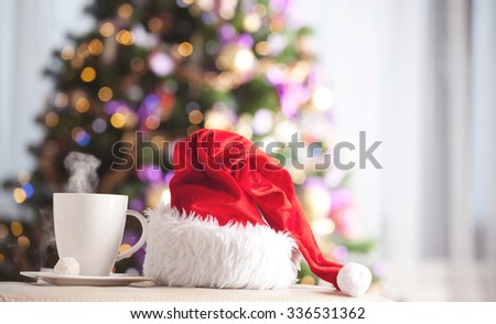 Santa Claus red hat and cup of tea in front of a christmas tree. Christmas background - stock photo