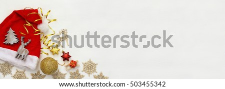 Santa claus red hat next to wooden decorations on white background. Website banner format