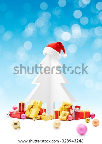 Santa Claus red hat on top of christmas tree with gifts and baubles - stock photo