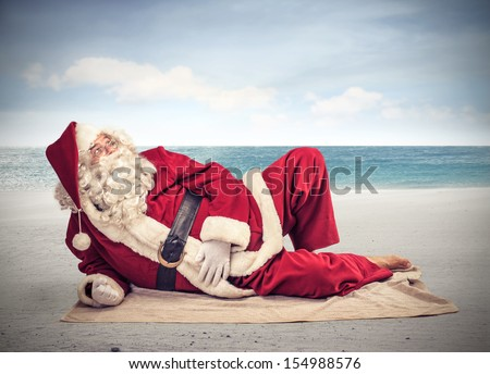 Santa Claus relaxes lying on the beach - stock photo