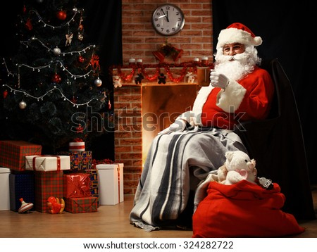 Santa Claus relaxing and having latte on background of Christmas tree - stock photo