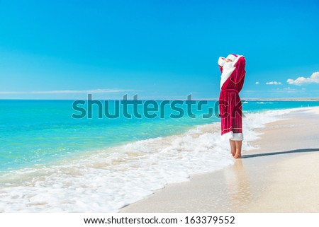 Santa Claus relaxing at sandy sea beach - Christmas concept - stock photo
