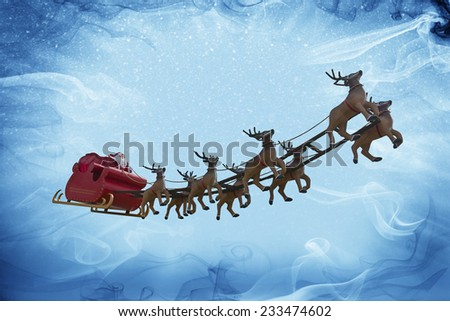 Santa Claus riding a sleigh led by reindeers on a colorful night with a full moon - stock photo
