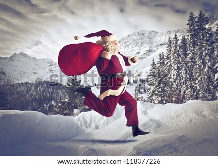 Santa Claus running on the snow with his sack of presents - stock photo