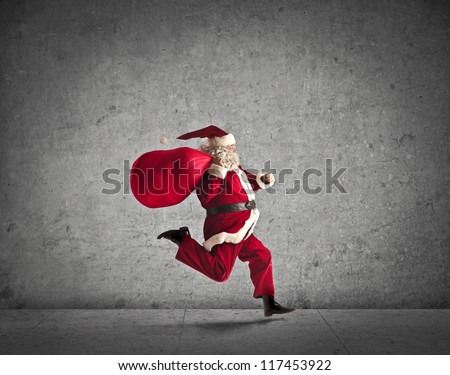 Santa Claus running with the bag of the presents - stock photo