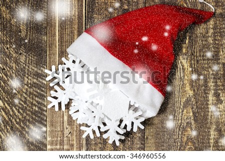 Santa Claus's cap and Christmas decorations on wooden texture - stock photo