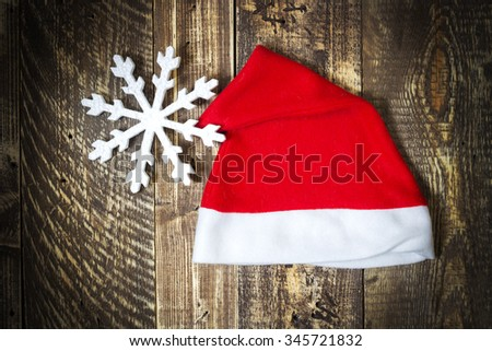 Santa Claus's cap and snowflake on wooden texture