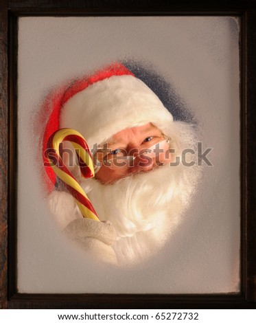 Santa Claus seen through a frosted window holding up a large candy cane. - stock photo