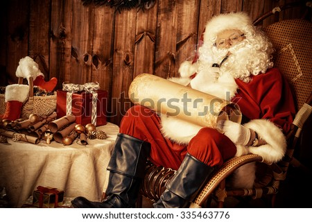 Santa Claus sitting at his wooden house in a comfortable chair, smoking a pipe and reading a letter.  - stock photo