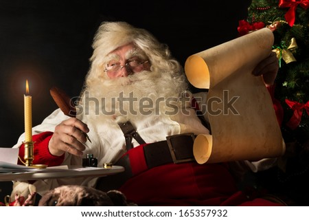 Santa Claus sitting at home and writing on old paper roll to do list with quill pen and ink at night with candle light. Authentic vintage style portrait. - stock photo