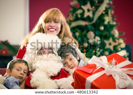 Santa Claus sitting between family with big present at home