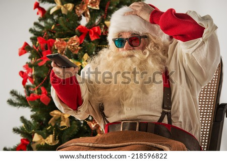 Santa Claus sitting in rocking chair near Christmas Tree at home and watching tv or home theater wearing 3d glasses and holding remote control - stock photo