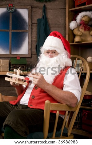 Santa Claus Sitting is a Rocking Chair in His Workshop Painting Toy Airplane. Vertical Composition.