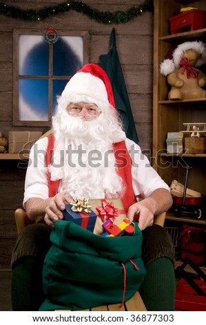 Santa Claus Sitting is a Rocking Chair with presents and toys in Bag. Vertical Composition - focus on Santa
