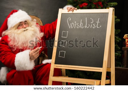 Santa Claus sitting near chalkboard with wishlist sign and blank copy space for checkboxes and your text - stock photo