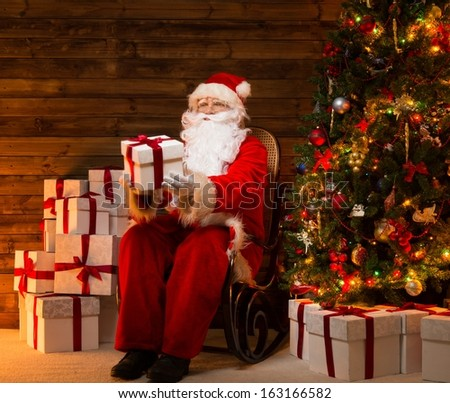 Santa Claus sitting on rocking chair in wooden home interior presenting gift box