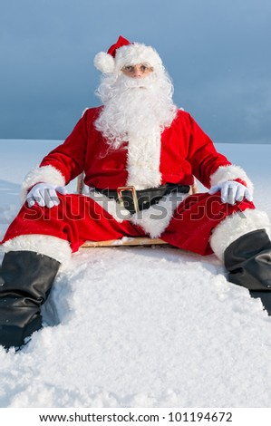 Santa Claus sitting on sunbed covered with snow - stock photo