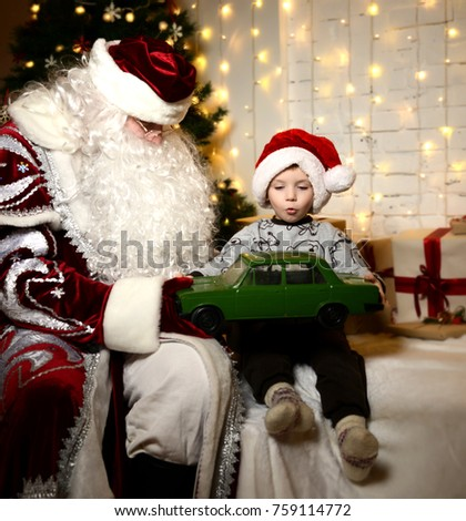 Santa Claus sitting with happy little cute baby boy kid near Christmas tree at home green retro car present