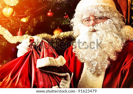 Santa Claus sitting with presents over Christmas background. - stock photo