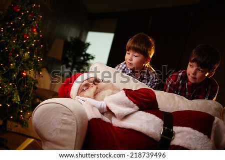 Santa Claus sleeping on sofa with two boys looking at him - stock photo