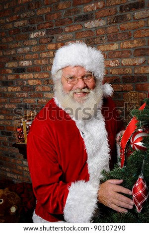 Santa Claus smiling as he is standing next to a Christmas Tree. - stock photo