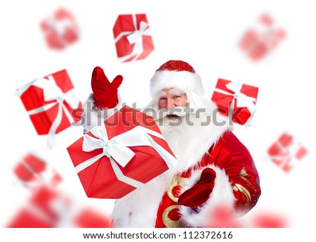 Santa Claus standing and doing magic. Gift boxes falling down around him - stock photo