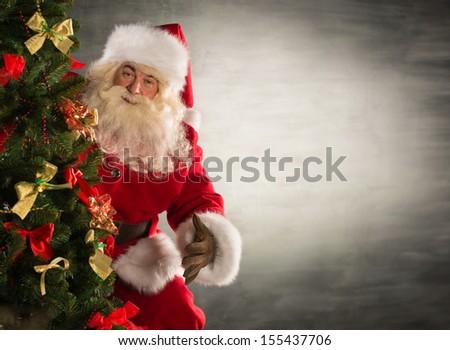 Santa Claus standing near Christmas tree. Lots of copyspace - stock photo