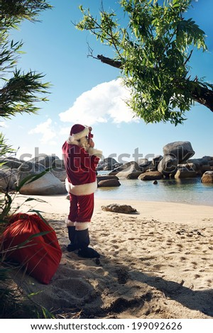 Santa Claus standing on a beach taking a picture of the view - stock photo
